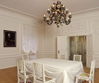 View of the table and chandelier in the White Hall, Urach Palace. Image: Landesmedienzentrum Baden-Württemberg, Sven Grenzemann